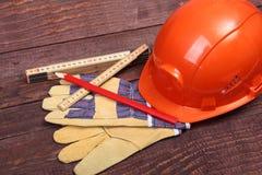 Orange hård hatt och handskar för arbete på wood bakgrund Arkivbilder
