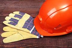 Orange hård hatt och handskar för arbete på wood bakgrund Royaltyfria Bilder