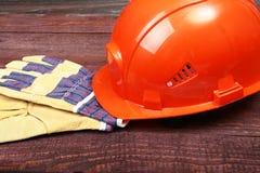 Orange hård hatt och handskar för arbete på wood bakgrund Arkivfoto