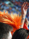A fan of the Netherlands national football team in wig among ordinary fans.Purchase the symbolics of fan to stand out from a crowd Stock Images