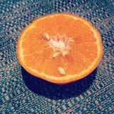 Orange. Half cut fruit with pips on a self-patterned blue and orange tinted fabric base Stock Image