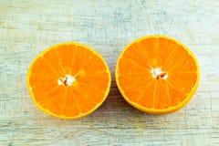 Orange half. Looks juicy put on wood background Royalty Free Stock Photography