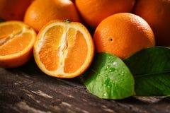 Orange, half of orange, orange lobule on the wooden table. Background Royalty Free Stock Images