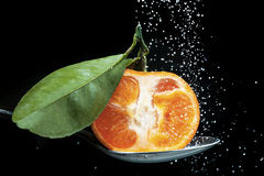 Orange half on spoon Royalty Free Stock Photography