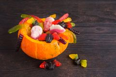 Orange halloween treak or treat container with candies. On wooden table wit copy space stock images