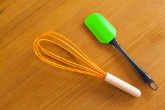 Orange hand whisk and green paddle on wooden background Royalty Free Stock Image