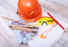 Orange hard hat, earplug, safety glasses and gloves for work. Earplug to reduce noise on a white background. Orange hard hat, earplug, safety glasses and gloves stock image