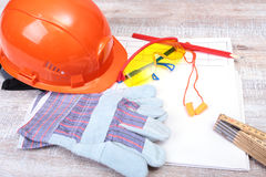 Orange hard hat, Earplug to reduce noise, safety glasses, gloves, pen and measuring tape on wooden background. Royalty Free Stock Image