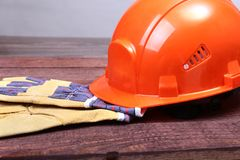 Orange hard hat and gloves for work on wood background. Royalty Free Stock Photography
