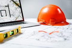 Orange hard hat, laptop  with drawings, level meter and protective glasses lying in a  blueprints on a table. Architectural and construction concept royalty free stock photo