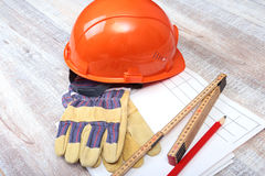 Orange hard hat, safety glasses, gloves and measuring tape on wooden background. Stock Photography