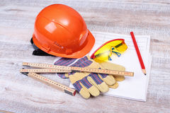 Orange hard hat, safety glasses, gloves and measuring tape on wooden background. Royalty Free Stock Photography