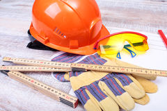 Orange hard hat, safety glasses, gloves and measuring tape on wooden background. you can place your text Stock Photography