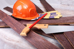 Orange hard hat, safety glasses, gloves and measuring tape for work on wooden background. Royalty Free Stock Photography