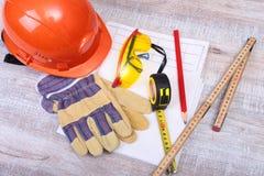 Orange hard hat, safety glasses, gloves, pen and measuring tape on wooden background. Stock Photo
