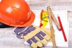Orange hard hat, safety glasses, gloves, pen and measuring tape on wooden background. Stock Images