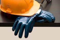 Orange hardhat and leather gloves royalty free stock photo