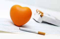 Orange heart, cigarettes and the cardiogram. Stock Image