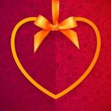 Orange heart shape frame hanging on silky ribbon Royalty Free Stock Images