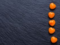 Orange heart shaped pills or candy on grunge black. Valentines day background. Orange heart shaped pills or candy on grunge black slate background. Copy space Stock Photography
