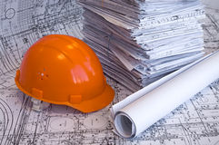 Orange helmet and heap of project drawings. Orange helmet and heap of design drawings are on the table. Business still-life Stock Photos