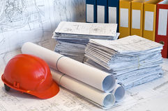 Orange helmet and heap of project drawings Stock Image