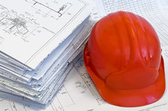 Orange helmet and heap of project drawings Stock Photography