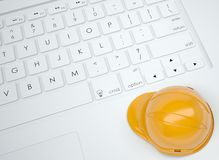 Orange helmet on the keyboard Royalty Free Stock Photos