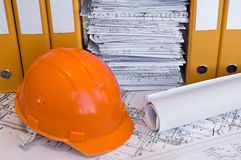 Orange helmet and project drawings. Orange helmet, design drawings and yellow file folders on the table. Business still life Royalty Free Stock Photography