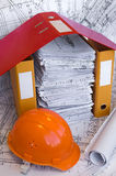 Orange helmet and project drawings. Orange helmet, design drawings and file folders on the table. Business still life Royalty Free Stock Photos