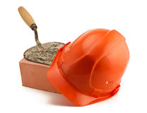 Orange helmet red brick and trowel. Orange helmet red brick and rusty bricklayer's trowel isolated on white stock image