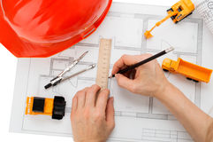 Orange helmet, ruler, pencil, drawing, construction equipment. All that is needed to start construction Stock Image