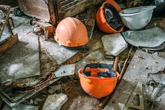 Orange helmets on dirty floor in abandoned factory, ruined economy concept Stock Images