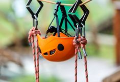 Orange Helmets and Strapping in the rope park. Adult and kids equipment for climbing in the adventure rope park. Active lifestyle stock photo
