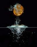 Orange Herausspringen des Wassers Stockbild