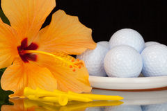 Orange hibiscus flower  and golf equipments on the glass table Royalty Free Stock Images