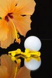 Orange Hibiscuse blühen und Golfausrüstungen auf dem Glastisch Stockfotos