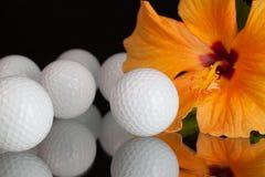 Orange Hibiscuse blühen und Golfausrüstungen auf dem Glastisch Lizenzfreie Stockfotos