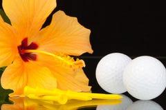 Orange Hibiscuse blühen und Golfausrüstungen auf dem Glastisch Stockbild