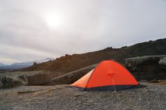 An orange high-altitude tent is set high in the mountains against the background of the Caucasian ridge. An orange high-altitude tent is set between stones high Royalty Free Stock Image