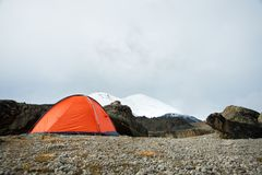 An orange high-altitude tent is set high in the mountains against the background of the Caucasian ridge. An orange high-altitude tent is set between stones high Stock Photo