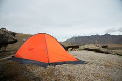 An orange high-altitude tent is set high in the mountains against the background of the Caucasian ridge. An orange high-altitude tent is set between stones high Royalty Free Stock Images