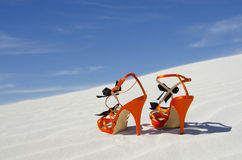 Orange high heels standing alone on sand dune. Close up of a pair of orange high heels standing lonely on white sand dunes, with  clear blue summer sky as Royalty Free Stock Photography