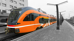 Orange high-speed train on the platform of the train station Stock Photo