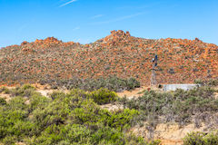 Orange hills. This is a scene from a remote farm in the Karoo, South Africa. There is a wind pump and water tank next to very red and orange rocks that are very Stock Photo