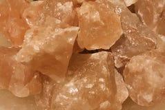 Orange Himalayan salt closeup background. Orange Himalayan salt pieces closeup warm effect background wallpaper stock image