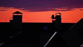 Orange Himmel und purpurrote Sonnenuntergangwolken bewegen sich über Stadtschräge Dächer stock video footage