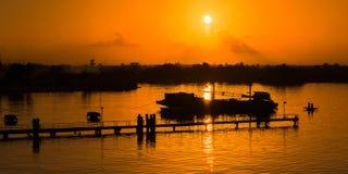Orange Himmelnatur des Sonnenunterganganlegestellenschattenbildes durch das Meer Stockbilder