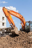 Orange Hitachi Digger Moving Soil Royalty Free Stock Photos