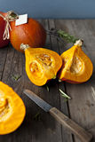Orange hokkaido pumpkins. Vibrant orange chopped pumpkins exposing the pulp. They are on rural wooden table surrounded with herbs and plants. Shallow depth of Stock Images